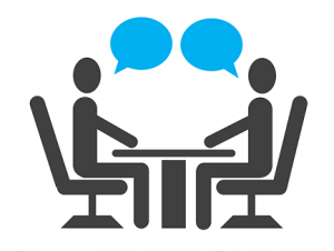 Clip art of two people talking across a table