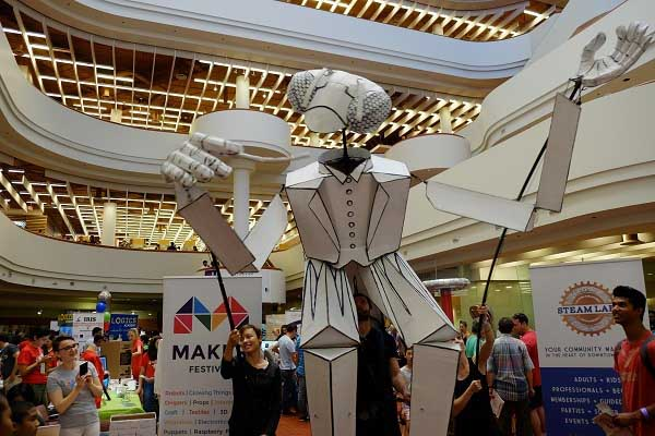 A large mantis puppet prays (typo deliberate) the crowd at the 2015 Maker Festival held at Toronto Reference Library.