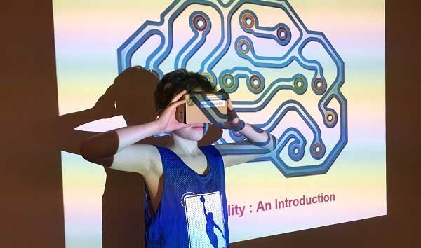 A youth at tries out the Knox V2 virtual reality cardboard viewer at TPL's Sanderson Library After School Youth Hub during March Break