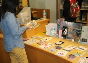 Student browsing through zines on a table at Seneca Libraries