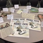 Secret Path by Gord Downie featured prominently on a table with newspaper clippings