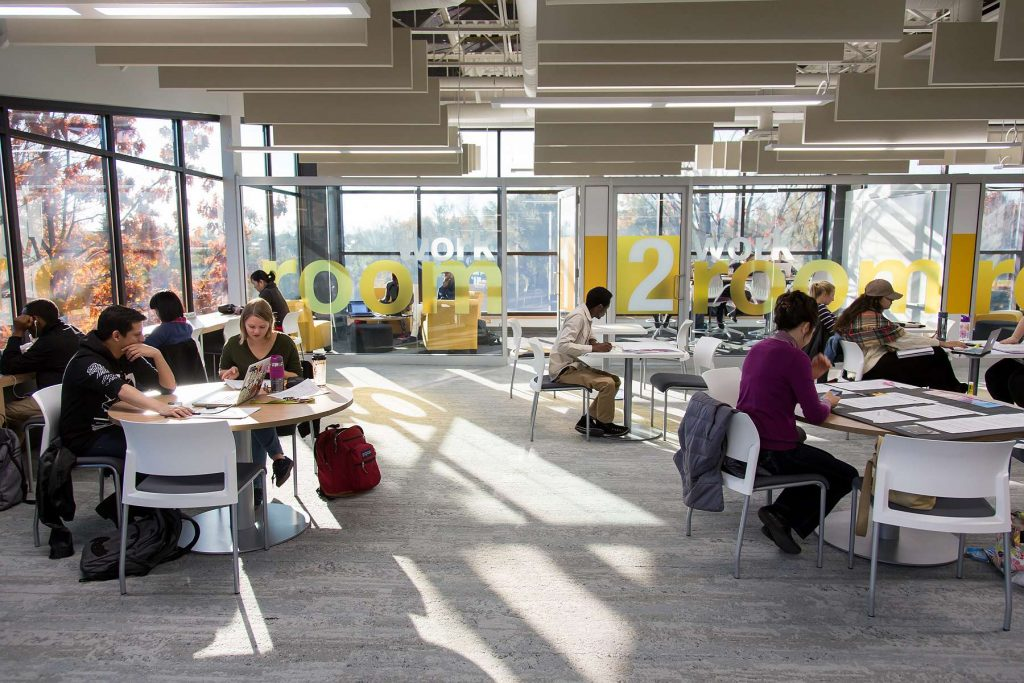Image of a busy library interior, students working at tables.