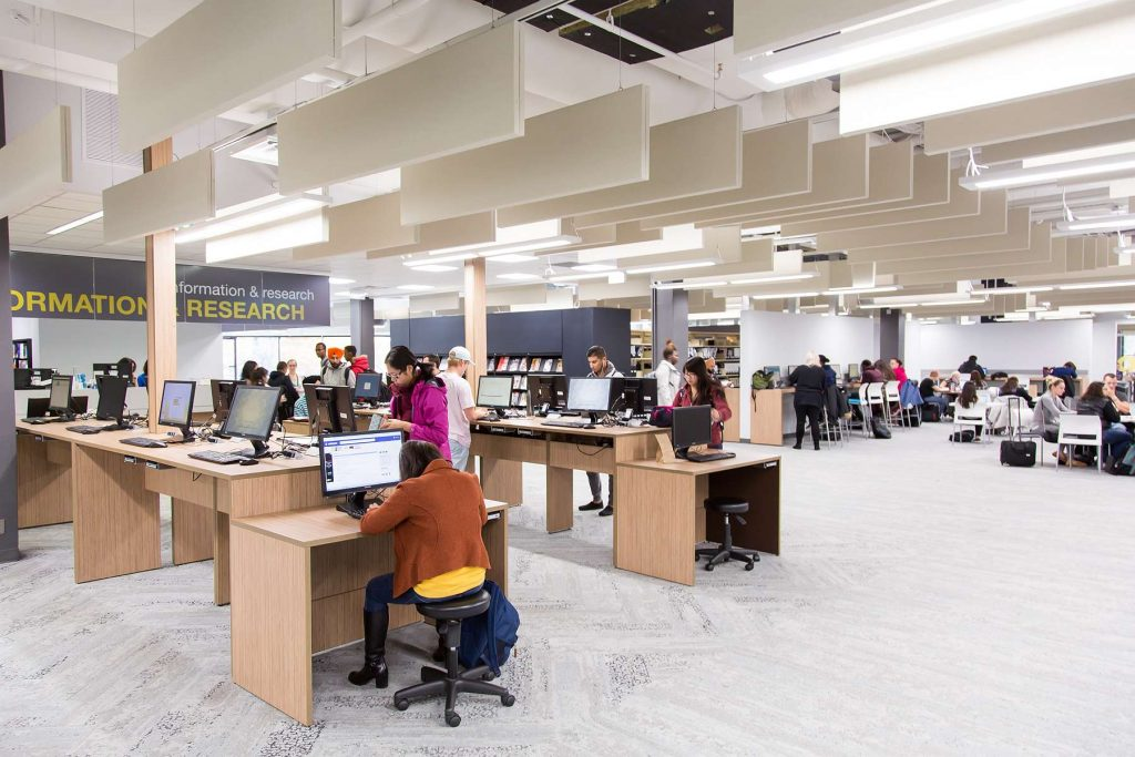Image of a library interior with computer workstations. Acoustic panels are hanging from the ceiling.